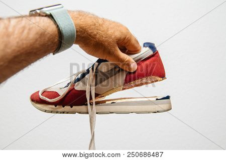 Man Holding Against White Background One Sport Footwear Sneaker With Broken Sole - Quality Manufactu