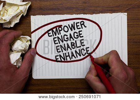 Text sign showing Empower Engage Enable Enhance. Conceptual photo Empowerment Leadership Motivation Engagement Hand hold paper lob and red pen red circled black words on white paper poster
