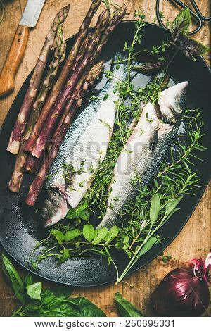 Cooking Fish Dinner. Flat-lay Of Raw Uncooked Sea Bass Fish With Fresh Herbs And Vegetables On Dark