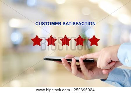 Man Hand Holding Smart Phone And Red Five Star Over Blur Background, Customer Excellent Rating Satis