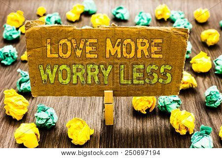 Text sign showing Love More Worry Less. Conceptual photo Have a good attitude motivation be lovable enjoy life Paperclip grip cardboard with texts many colorful lobs scattered on wooden desk poster