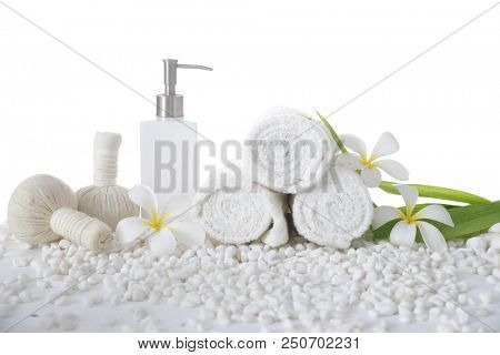 White frangipani with rolled towel ,bottle oil with herbal ball ,leaf on pile of white stones