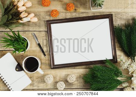 Wood picture frame, diary and coffee with flower decoration on wood background. Rustic nostalgia flat lay. poster