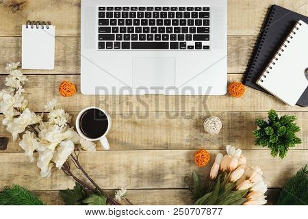 Laptop, notebook, diary and coffee with flower decoration on wood background. Rustic nostalgia flat lay. poster