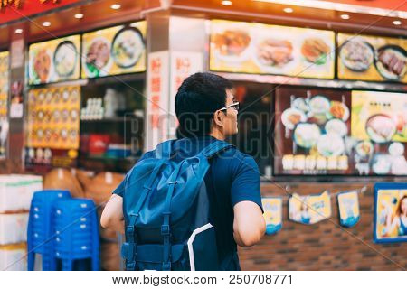 Young Man Traveler Is Visiting At Mongkok In Hong Kong For Find Some Restaurant For Eat Noodles.