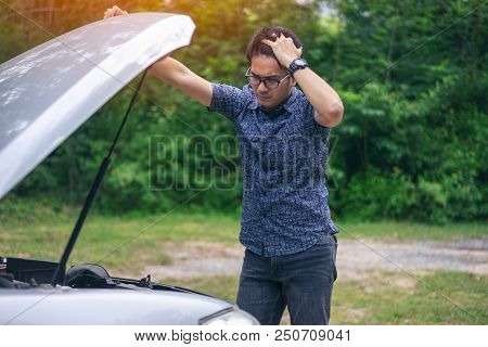 Young Asian Handsome Man Standing By The Broken Down Car And Waiting For Help With Strain Face And S