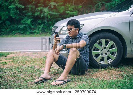 Young Asian Handsome Man Sitting On The Floor By The Broken Down Car And Waiting For Help With Strai