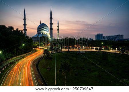 Sunrise Scene Of Light Trails Of Car On The Road Into Blue Mosque Or Sultan Salahuddin Abdul Aziz Sh