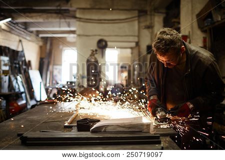 Young contemporary blacksmith standing by iron anvil and processing workpiece with electric handtool poster