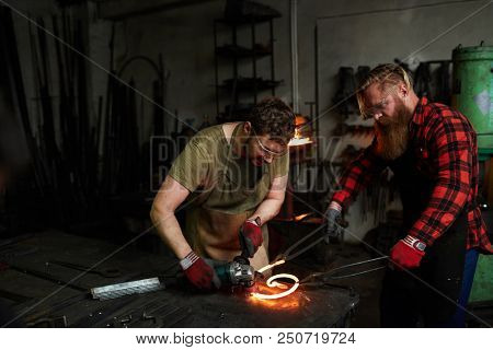 Two professional blacksmiths in workwear standing by anvil and processing hot iron workpiece in smithy