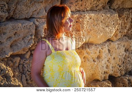 A Portrait Of A Beautiful Caucasian Pregnant Woman In Her Early 30s In A Yellow Dress With An Ancien
