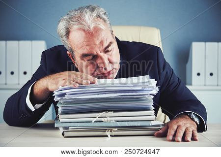 Bored Aged Male In Dark Elegant Suit Sitting On Office Chair Resting With Closed Eyes On Large Pile