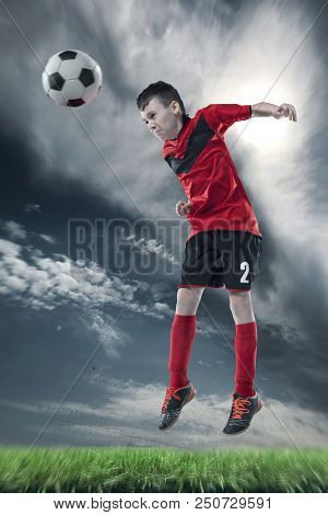 Football Player Hitting The Ball With Head On A Soccer Field