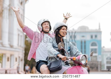 Feel Freedom. Jovial Pretty Couple Wearing Helmets And Man Rising Hands