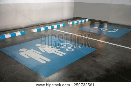 The International Sign For Family And A Handicapped Parking Stall In A Parking Lot.