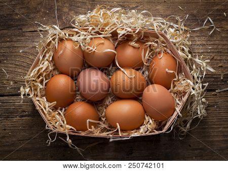 Set Of Chicken Eggs In Sawdust Nest On Wooden Background