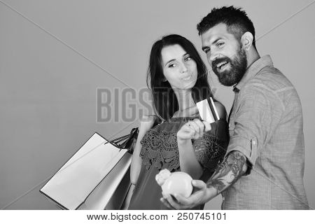 Shopping And Free Time Concept. Couple Holds Shopping Bags On Grey Background. Man With Beard Holds