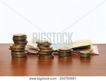 The Ukrainian Money - Four Rouleaux And Paper Hryvnias Against. Metal Coins Close Up - The Ukrainian