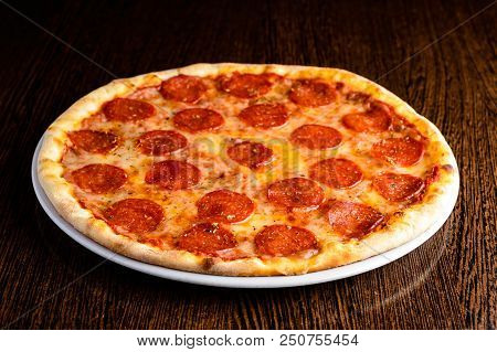Delicious Hot Homemade Pepperoni Pizza On The Wooden Table