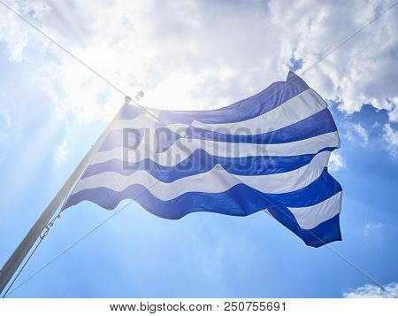 Official flag of Greece waving on a cloudy sky and sunlight rays.