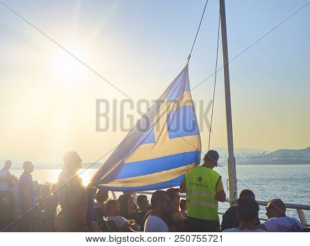 Athens, Greece - July 2, 2018. Operators lowering a official flag of Greece at sunset.