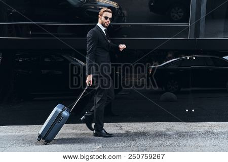 Confident Businessman. Full Length Of Young Man In Full Suit Pulling Luggage And Checking The Time W