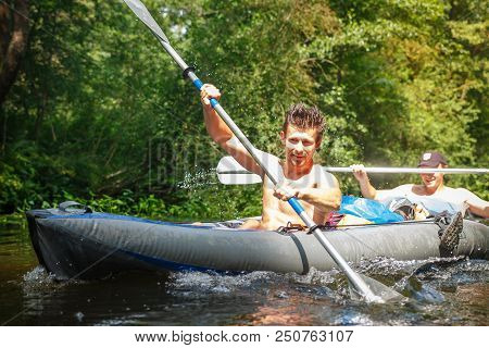 Two Rowers In Boat With Oars In Hands On The River On Summer Day. Young Sports Guys Swim A Canoe Alo