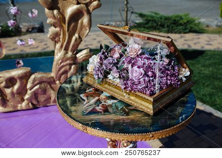 Casket With Purple Flower On Wedding Ceremony Decor With Gold Luxury Frame On Table. Bride And Groom