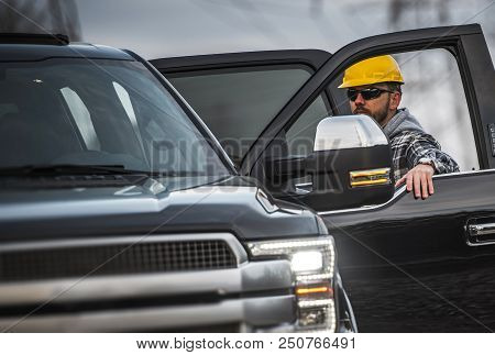 Hard Working Caucasian Men Wearing Yellow Helmet. Industrial Theme. Worker And His Corporate Pickup