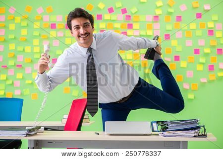 Man in the office with many conflicting priorities doing exercis