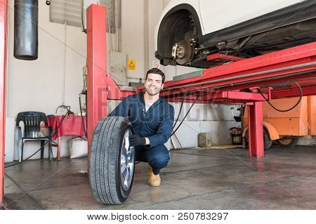 Smiling Mechanic Examining Car Tire While Crouching In Workshop