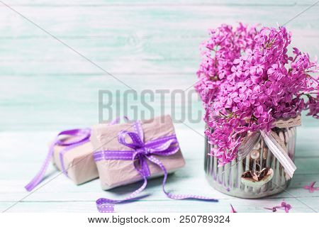 Violet  Lilac Flowers In Vase And Boxes With  Presents On Turquoise Background. Selective Focus. Pla