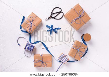 Empty Tag And Wrapped  Gift Boxes With Presents  On  White Textured Background. Selective Focus Is O