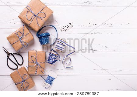Wrapped  Gift Boxes With Presents, Scissors,  Blue Ribbon  And Tags On Textured White Wooden Backgro