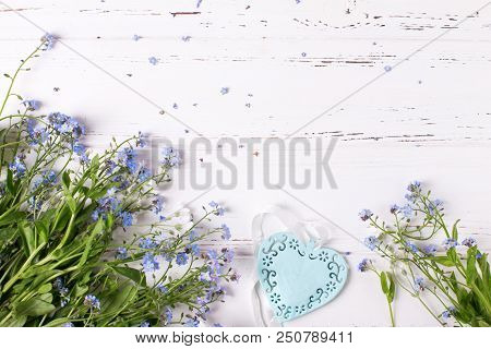 Border From  Blue Forget-me-nots Or Myosotis Flowers And Heart On  White Wooden Background. Floral S