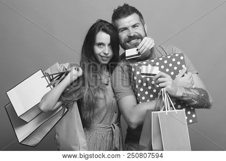 Couple In Love Hugs Holding Shopping Bags And Credit Cards On Blue Background. Bearded Man With Smil