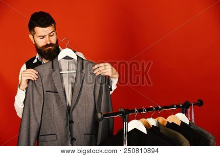 Man Looks For Clothes At Fashion Shop. Bearded Hipster Man Stands Near Rack With Clothes Against Red