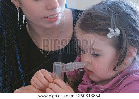 Little cute girl inhaling through inhaler mask with her mom. Use nebulizer and inhaler for the treatment poster
