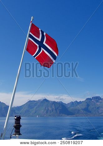 Flag Of Norway On The Blue Sky And Mountainds Background.
