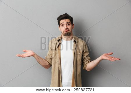 Portrait of a confused young casual shrugging shoulders isolated over gray background