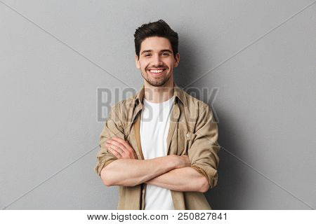 Portrait of a happy young casual man standing with arms folded isolated over gray background