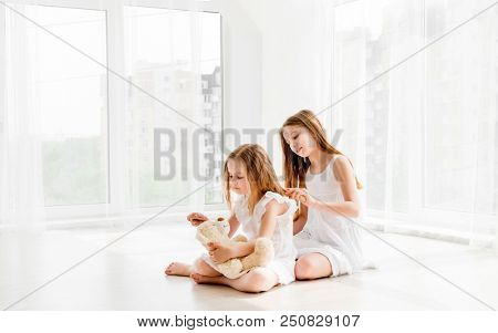 Lovely little girl brushing hair of her younger sister while sitting on the floor. Little child girl playing with bear toy while her older sister combing her hair