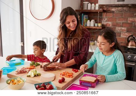 Children Helping Mother To Make School Lunches In Kitchen At Home