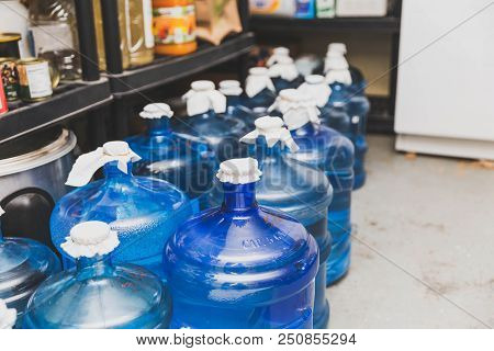 Large Blue Water Bottles In A Food Storage Area. Bottles Have Temporary Fabric Lids.