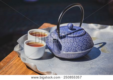 Blue Tea Kettle With Intricate Design Details And White Tea Cups On A Metal Tray Outdoors.