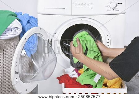 Male Loading Dirty Clothes From Basket To Washing Machine For Washed. Home Appliance