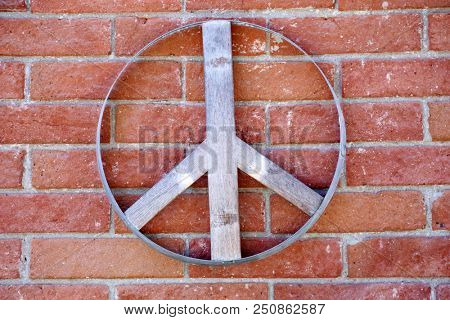 Peace Sign. A wooden peace sign on a brick wall outdoors.