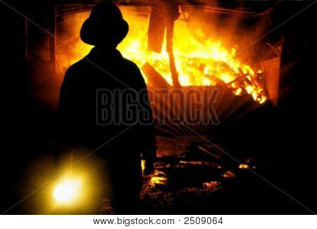 Fireman At Work Fighting Fire At Night