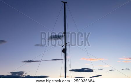 Sailing concept. Mast of a sailing boat at sunset, wallpaper and copy space.