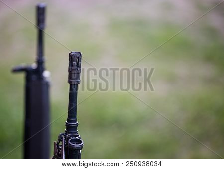 Firearm handgun. Front side of weapon with close up view on blurred nature background.